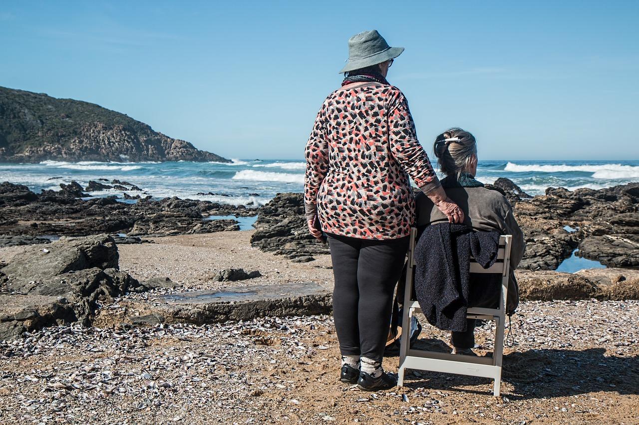 senior women, sitting on a beach